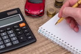 Calculadora, planilha de custos, moedas e miniatura de carro sobre mesa | Pagamento do DPVAT separado do IPVA em 2018