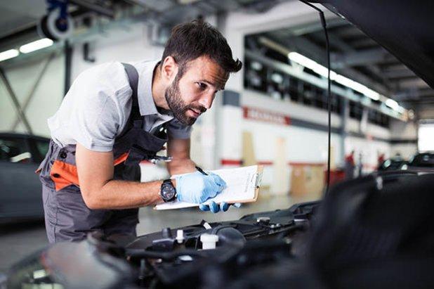 Homem olhando motor de carro | Como funciona o redutor de pressão do GNV