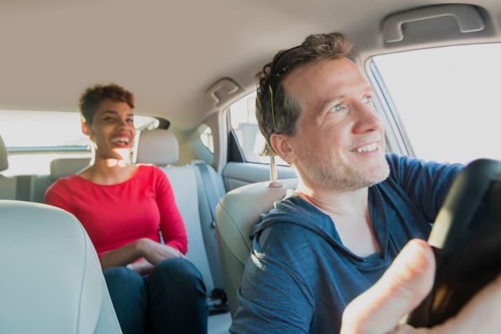 Motorista conduzindo passageira | Economize usando GNV para transporte de passageiros