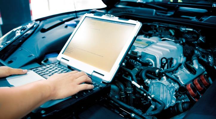 Mecânico com notebook sobre o motor de um carro | O que é emulador de bico injetor?