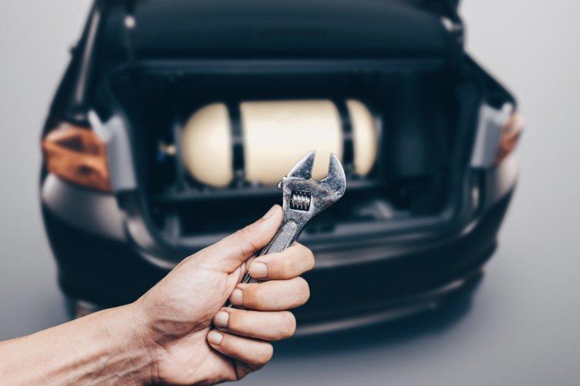 Carro com cilindro de gnv na mala atrás de uma mão branca masculina segurando uma ferramenta | Quais são as vantagens do kit gás de 5ª geração?