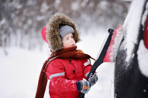 Criança com escova tirando neve da lateral de um carro | Cuidados com o carro no inverno