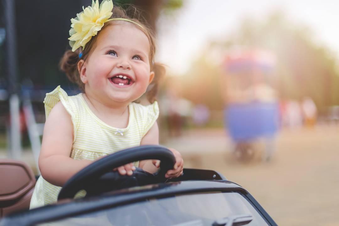 Menina branca de vestido amarelo sorrindo dirigindo um carro de brinquedo | Saiba por que o GNV é seguro
